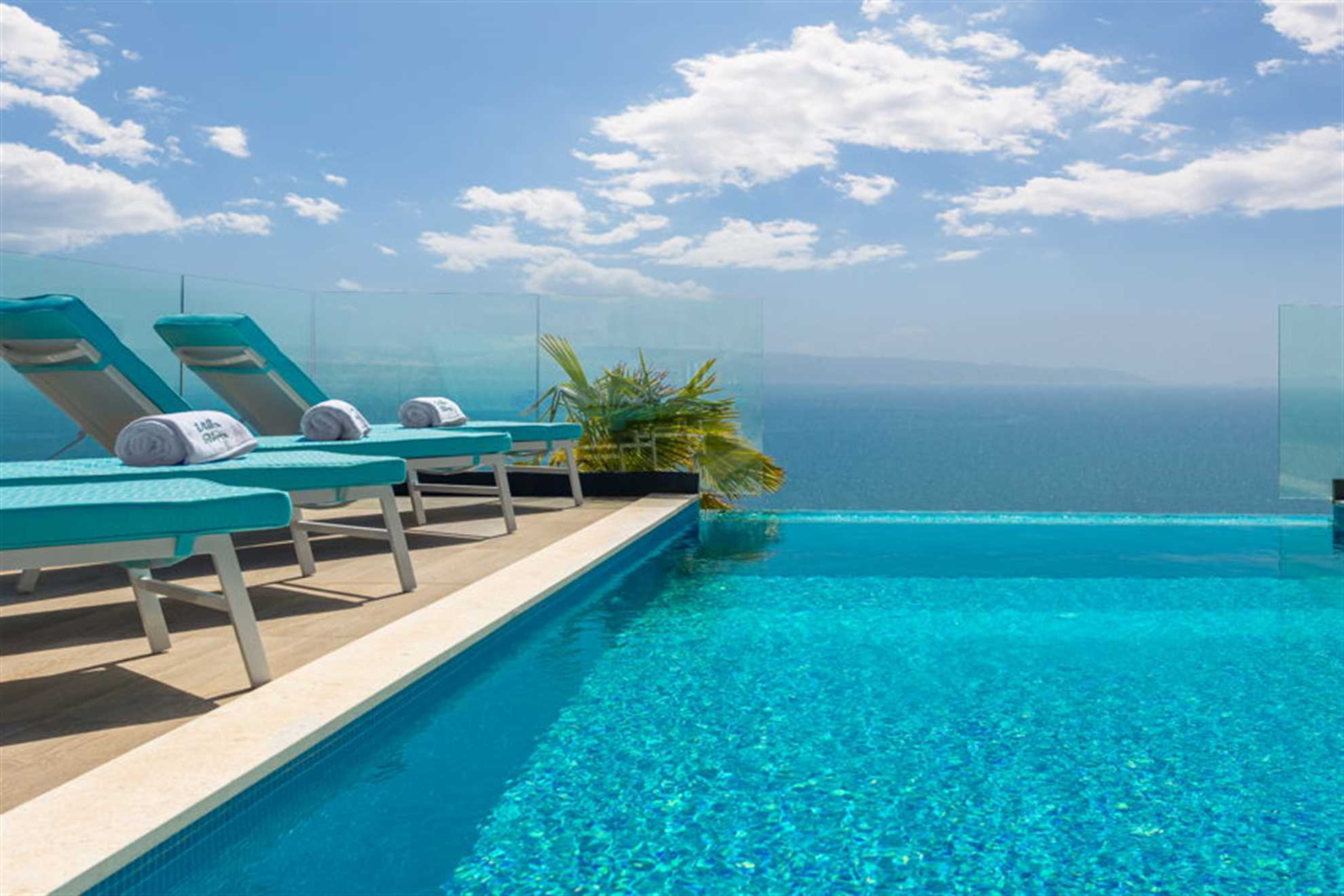 Beautiful sea view from pool terrace equipped with deck chairs